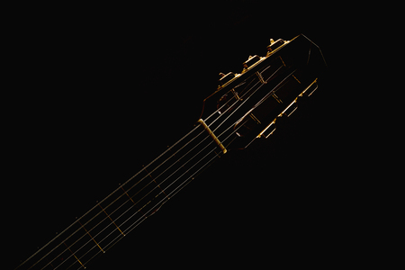 Neck and strings of gypsy acoustic guitar in the dark, accentuated shapes.