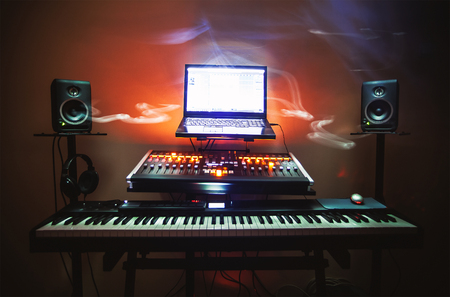 Closeup view on small modern home music studio, keyboard, mixing console and computer. 免版税图像