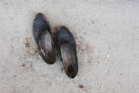 Closeup view of an old and dirty rubber shoes on asphalt, abstract composition.