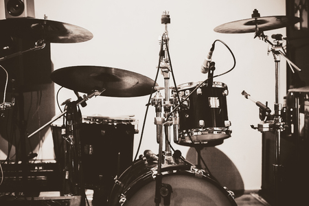 Ordinary scene from a home studio, mics on drums in black and white.