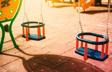 Details of modern and colorful rocking chair, scene from park during sunny day. Imagens