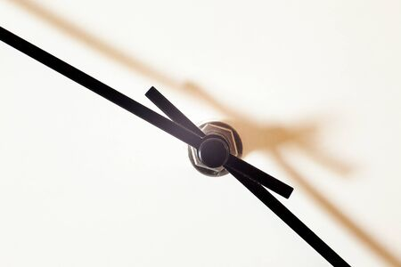 Closeup view of a simple wall watch, details of minute and hour hands on white
