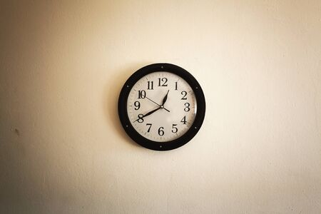 Old vintage style clock on old white wall.