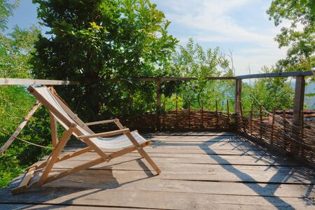 Old wooden armchair on wooden balcony, during sunny day.