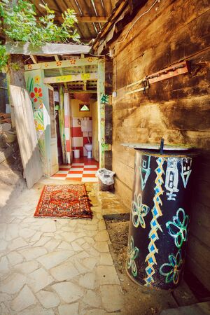 Part of an old village household, details of colorful toilet and bathroom entrance. Foto de archivo - 129245980