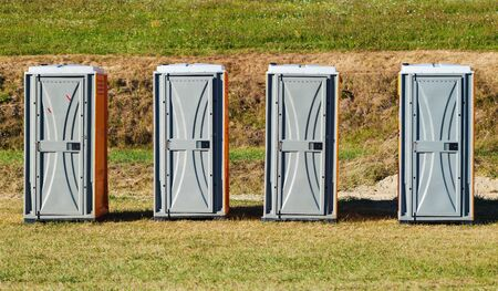 Four toilets on green field during sunny day. Foto de archivo - 129245870