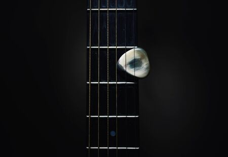 Details of an old acoustic guitar, Django style, closeup view of neck and handmade pick. 版權商用圖片