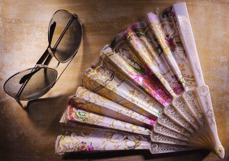 Decorative fans and sunglasses on wooden board. Фото со стока