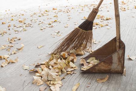 Barrer las hojas de otoño en la carretera. Foto de archivo