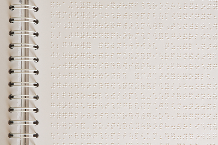 braille: Close up of paper page with braille text.