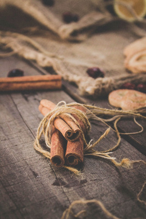 string together: Bunch of cinnamon sticks on wooden table