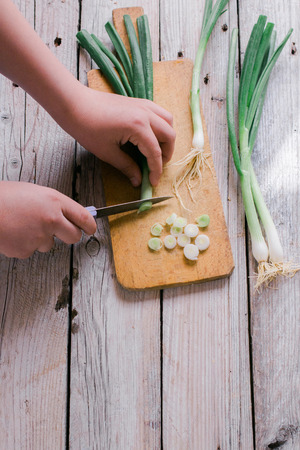green onions: Cutting green onions on a wooden background Stock Photo