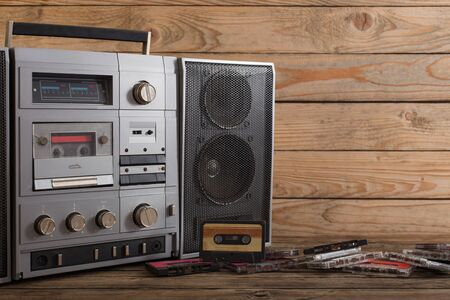 old tape recorder and cassette on  wooden background