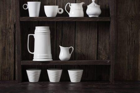white kitchen dishware on old dark wooden background