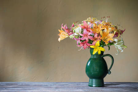 lily in ceramic green jug on background wall