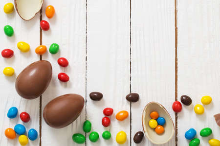 Easter chocolate eggs and candies on white wooden background
