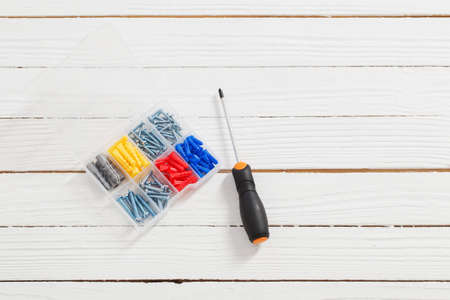 screwdriver and dowels on white wooden background