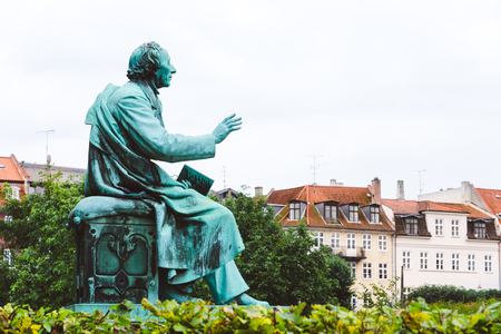 Hans Christian Andersen statue in Rosenborg garden, Copenhagen, Denmark. Bronze sculpture of famous danish fairy tale writer looking toward danish house roofs.