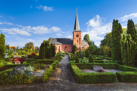 gravestones: Old city cemetary and catholic church in Dragor, Denmark - September, 21th, 2015. Gravestones, greenery and cloud sky at the early morning in fishman village near Copenhagen. Editorial