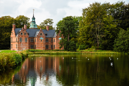 bath house: Hillerod, Denmark - September, 24th, 2015. Bath House hunting lodge reflected on the lake water near Frederiksborg castle. Romantic park around lonely pond with water birds.