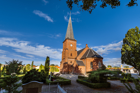 gravestones: Old city cemetary and catholic church in Dragor, Denmark - September, 21th, 2015. Gravestones, greenery and cloud sky at the early morning in fishman village near Copenhagen. Stock Photo