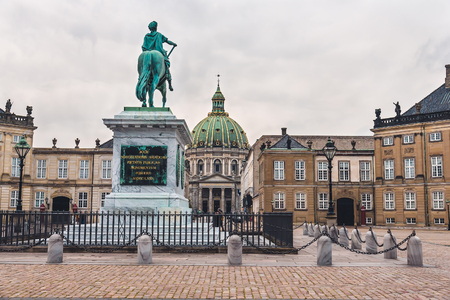 royal family: Copenhagen, Denmark - September, 23th, 2015. King statue and Amalienborg palace. Home of Danish royal family consists of four classical palace facades around the octagonal yard.