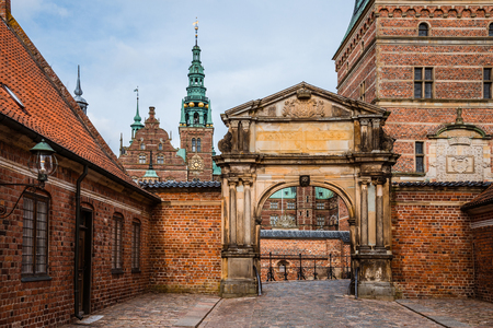 spiel: Copenhagen, Denmark - September, 24th, 2015. Entrance to Frederiksborg palace. Red brick fortress wall, archway and green copper spiels of towers of renaissance castle Frederiksborg.