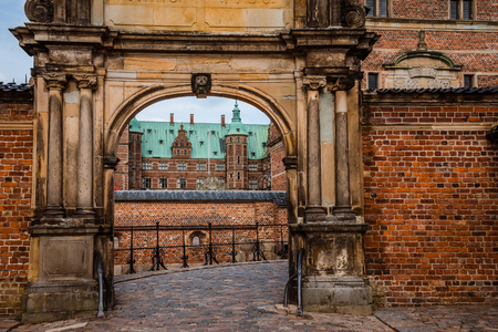 spiel: Hillerod, Denmark - September, 24th, 2015. Entrance to Frederiksborg slot near Copenhagen. Red brick fortress wall, archway and green copper spiels of towers of renaissance castle Frederiksborg. Editorial