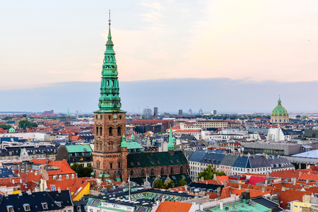 spiel: Copenhagen skyline by evening. Denmark capital city streets and danish house roofs panoramic view from top of Christiansborg palace.. Copenhagen old town, Nikolaj Church spiel and Amalienborg dome.