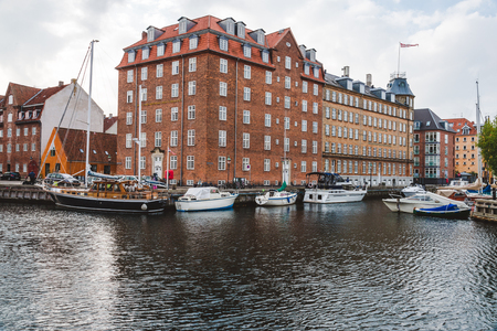 September, 24th, 2015 - Copenhagen, Denmark. Christianshavn harbor with colorful scandinavian houses and private boats reflected on the water of canal.