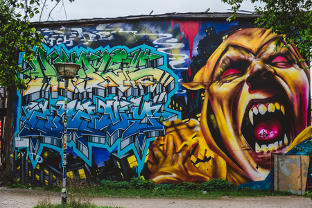 September 24th, 2015 - Christiania district in Copenhagen, Denmark. Evil face street graffiti in Freetown Christiania - self-proclaimed autonomous hippie commune republic at Christianshavn area.