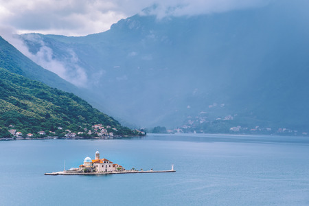 Catholic Church Of Our Lady Of The Rocks on Our Lady Of The Rocks island and Boka Kotorska landscape. One of the two islets near coast of Perast town at Kotor bay, Montenegro.