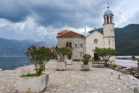 Roman Catholic Church Of Our Lady Of The Rocks  on Our Lady Of The Rocks island. One of the two islets near coast of Perast town at Kotor bay. Gospa Od Skrpeja - tourist attraction in Montenegro. Stock Photo
