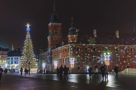 night before christmas: Warsaw, Poland - December 24th, 2016. Warsaw old town at winter night before Christmas and New year holidays. The Royal Castle, Xmas tree and market square surrounded by historical buildings.