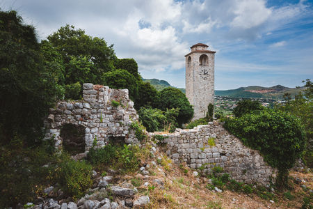Ancient stone ruins and clock tower at Old Bar town, Montenegro. Stari Bar - ruined medieval city on Adriatic coast, Unesco World Heritage Site. Stock Photo