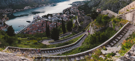 Kotor Bay and Old Town panoramic landscape from above Kotors castle of San Giovanni. Stone staircase, traditional house roofs, ancient fortress wall and Boka Kotorska wide angle view.