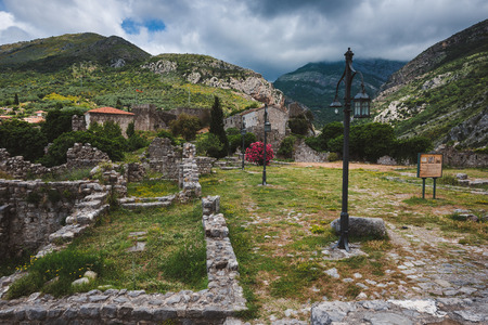 Cloudy mountains and ancient stone ruines of Old Bar town, Montenegro. Stari Bar - ruined medieval city on Adriatic coast, Unesco World Heritage Site. Stock Photo