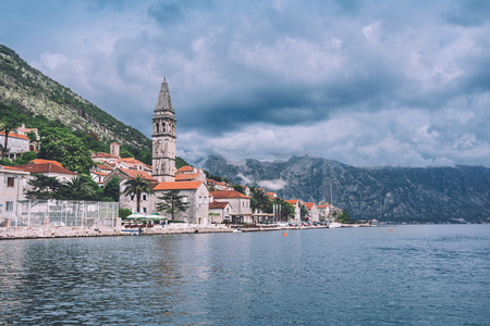 Famous ancient Perast village on Kotor bay by cloudy day in Montenegro. View to Perast Old Town roofs and mountains from water of Boka Kotorska. Postcard montenegrin landscape. Stock Photo