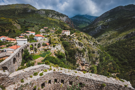 Rocks, ancient stone aqueduct and fortress wall of Old Bar town, Montenegro. Stari Bar - ruined medieval city on Adriatic coast, Unesco World Heritage Site. Stock Photo