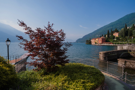 milánó: Panoramic view of Como lake shore and Bellano fishing village. Italian waterfront houses, wooden pier and mountains in small coast town Bellano, Lombardi, Italy. Stock fotó