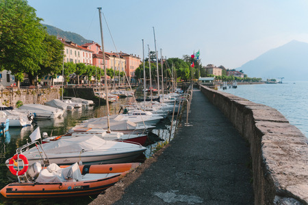 milánó: June 13th, 2017 - Lombardy, Italy. Coastline of Bellano fishing village, situated on Como Lake shore. Traditional italian houses, boats in port and embankment in small coast town Bellano. Sajtókép