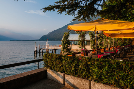 milánó: June 13th, 2017 - Lombardy, Italy. Waterfront restaurant in Bellano fishing village, situated on Como Lake shore. Cafe tables, lake and mountains view by sunset in small coast town Bellano. Sajtókép