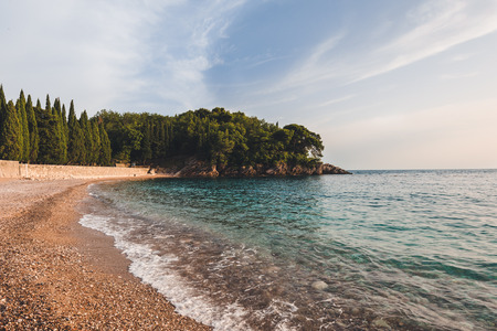 Wide angle view of Milocer Park and Royal beach near Sveti Stefan, Montenegro. Evening landscape with Adriatic sea, evening tide and private Kings and Queens beach with mountains.
