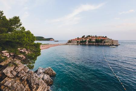 stephen: Sveti Stefan island and beach near Budva, Montenegro on Adriatic coast. Evening view of Adriatic sea, St. Stefan luxury fortificated village and private beach. Stock Photo