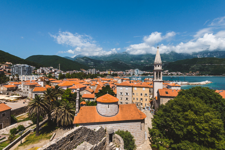 Budva Old town panorama with city roofs, St.John church spire, cloudy mountains and Adriatic sea on background. Tourist capital Budva wide angle high view from above the vantage point, Montenegro. Stock Photo