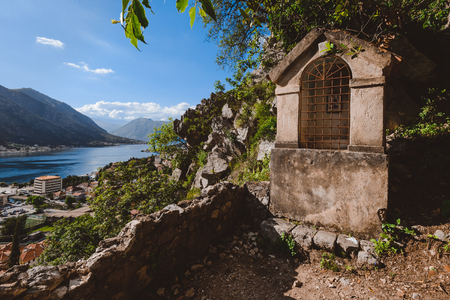 Small stone shrine on the path to Kotors castle along the fortress wall. Kotor Bay, Old Town and mountain view on the background. Stock Photo