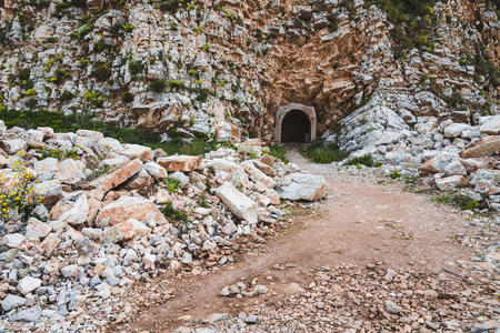 threw: Entrance to the mountain tunnel on the way from Perazica Do to Petrovac, Montenegro. Wild rocks and stones on the path threw the mountain.