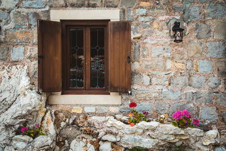 Ancient stone wall, classic old window with wooden shutters, street lantern and flowers on Petrovac, Montenegro.
