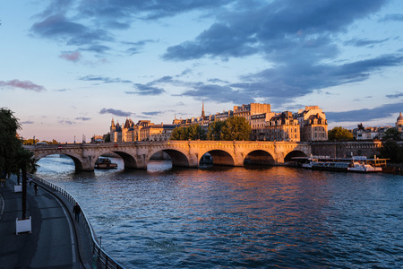 Paris, France - August 13, 2016. Sunset over Seine river, Pont Neuf bridge and Cite island with Royal palace, Conciergerie and medieval buildings. Evening Paris cityscape panoramic view. Editorial