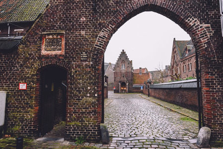 New Saint Elisabeth beguinage entrance in Sint-Amandsberg district, Ghent, Belgium. Known as Groot Begijnhof Sint-Amandsberg. Brick belgium houses, cobbled street and archway by rainy day in Gent. Editorial